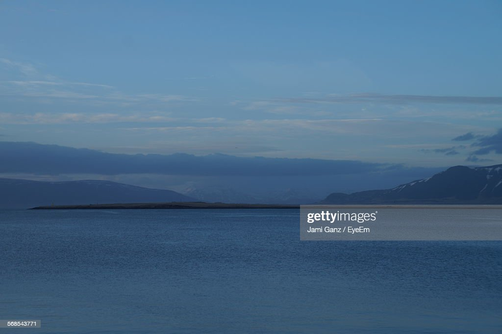 Scenic View Of Sea And Mountain Against Blue Sky : Stock Photo