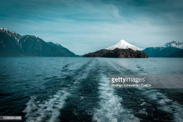 scenic view of sea and mountain against sky during winter - petrohue river stock photos and pictures