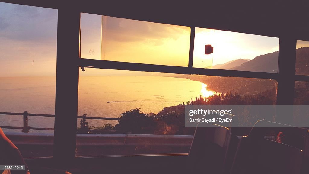 Scenic View Of Sea And Mountain Against Sky Seen Through Bus : Stock Photo