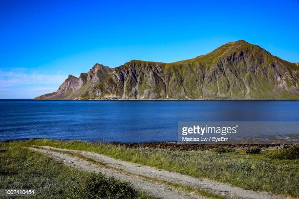 Scenic View Of Sea And Mountains Against Blue Sky