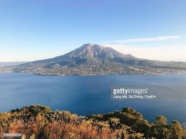 scenic view of sea and mountains against blue sky - 鹿児島県 ストックフォトと画像