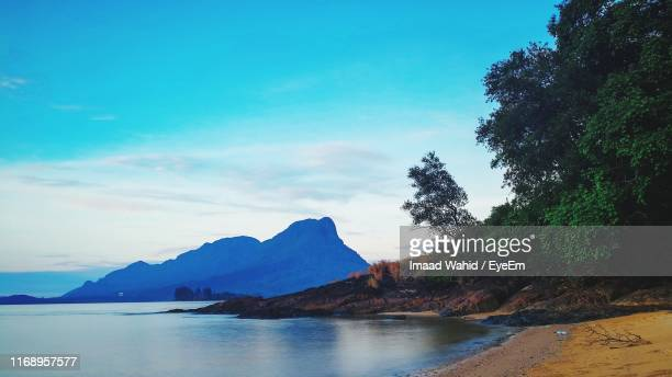 scenic view of sea and mountains against blue sky - sarawak state stock pictures, royalty-free photos & images