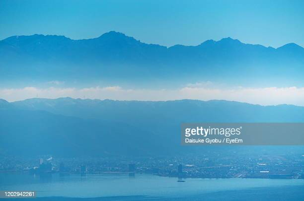scenic view of sea and mountains against blue sky - 諏訪市 ストックフォトと画像