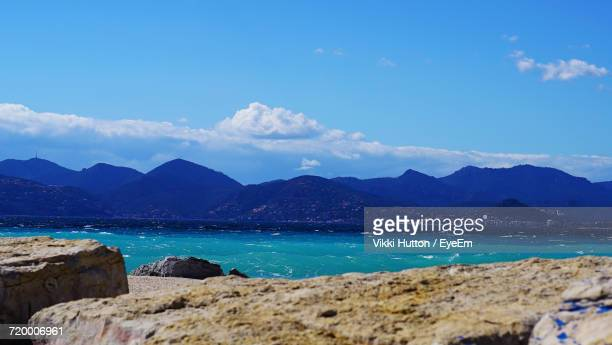 scenic view of sea and mountains against blue sky - hutton stock photos and pictures