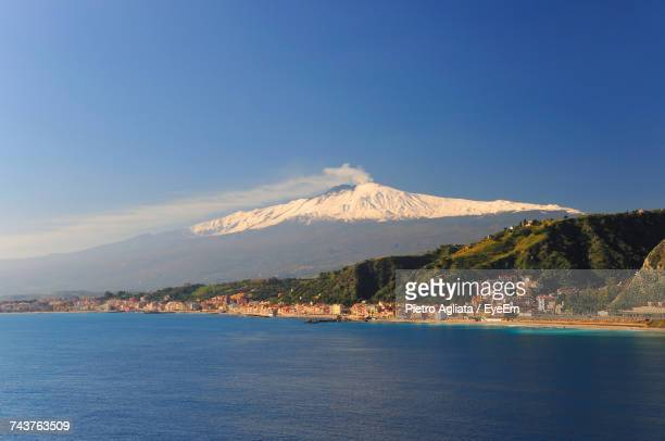 scenic view of sea and mountains against blue sky - catania stock photos and pictures