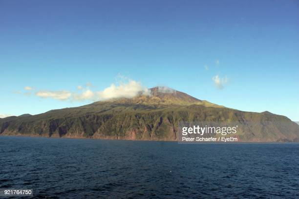 scenic view of sea and mountains against blue sky - tristan da cunha eiland stockfoto's en -beelden