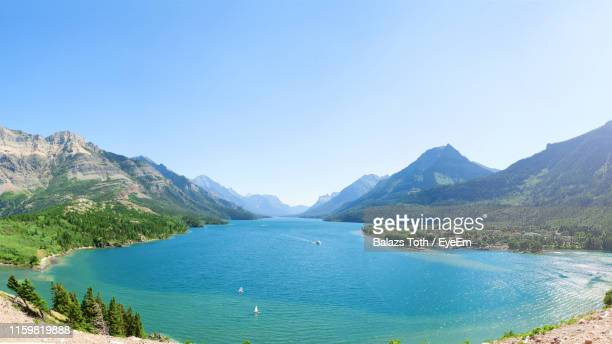 scenic view of sea and mountains against clear blue sky - giornata mondiale della terra foto e immagini stock
