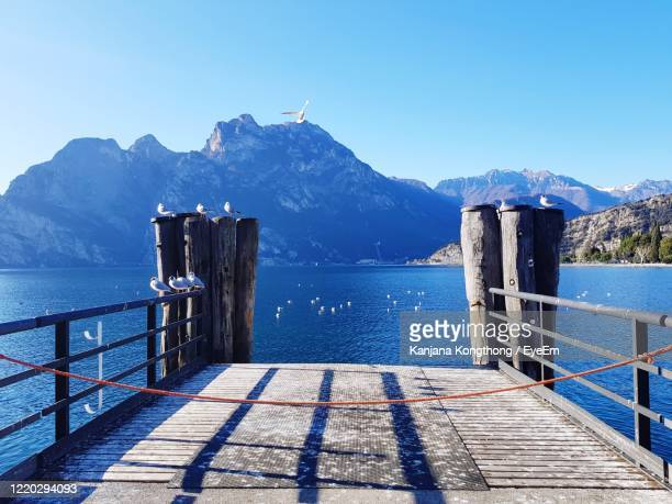 scenic view of sea and mountains against clear blue sky - kanjana kongthong foto e immagini stock