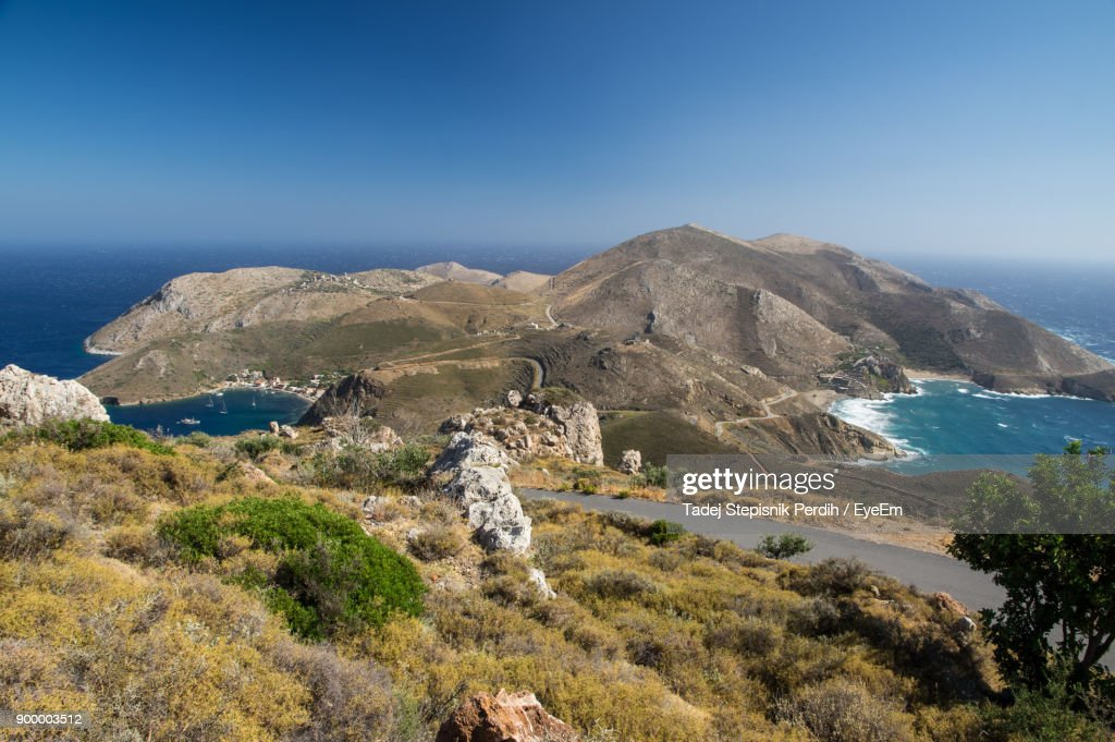 Scenic View Of Sea And Mountains Against Clear Blue Sky : Stock Photo