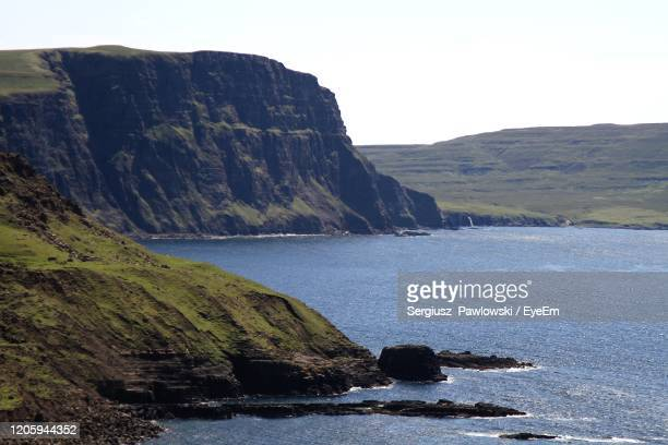 scenic view of sea and mountains against clear sky. neist point lighthouse. - hebriden inselgruppe stock-fotos und bilder