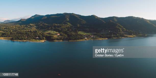 scenic view of sea and mountains against clear sky - bortes stock-fotos und bilder