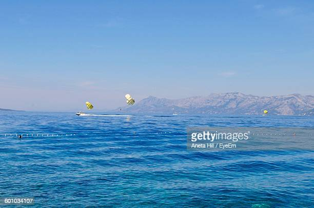 Scenic View Of Sea And Mountains Against Clear Sky