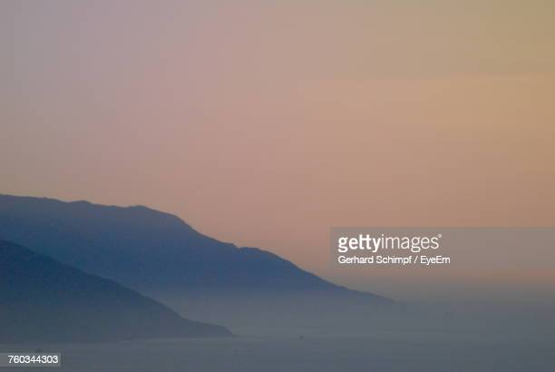 scenic view of sea and mountains against clear sky - gerhard schimpf stock photos and pictures
