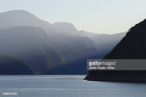 scenic view of sea and mountains against clear sky,fv,norway - james popple stock pictures, royalty-free photos & images