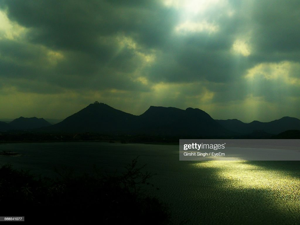 Scenic View Of Sea And Mountains Against Cloudy Sky : Stock Photo