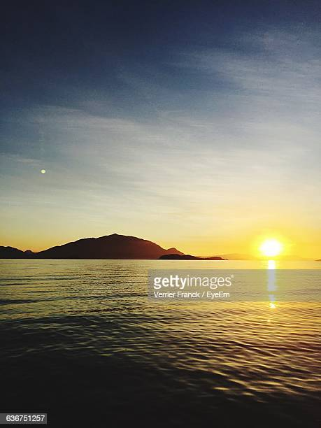 Scenic View Of Sea And Mountains Against Sky During Sunset