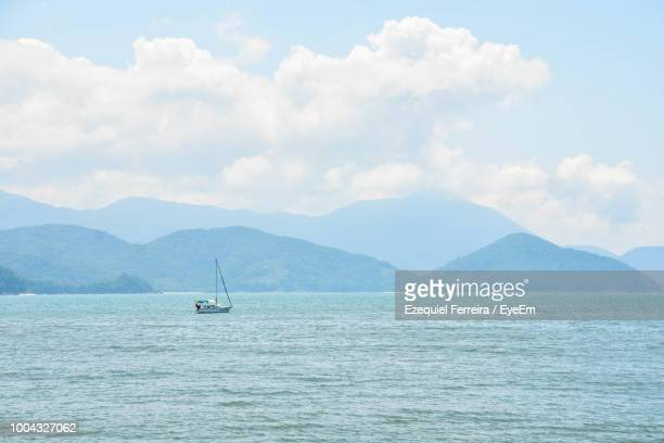 Scenic View Of Sea And Mountains Against Sky
