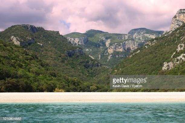 scenic view of sea and mountains against sky - land in sicht stock-fotos und bilder
