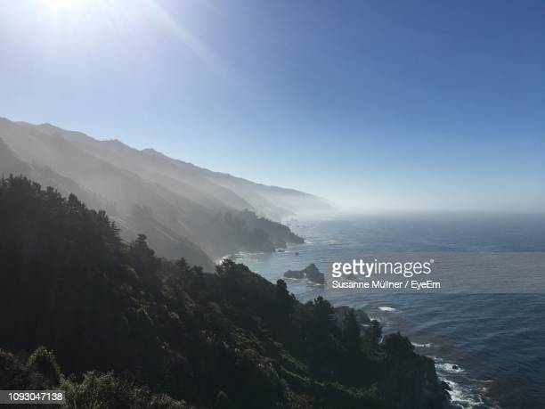 scenic view of sea and mountains against sky - big sur stock pictures, royalty-free photos & images