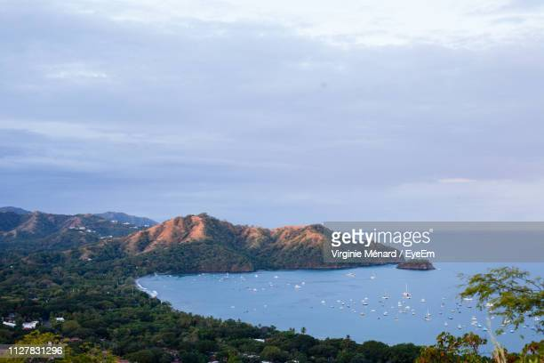 scenic view of sea and mountains against sky - bahía fotografías e imágenes de stock