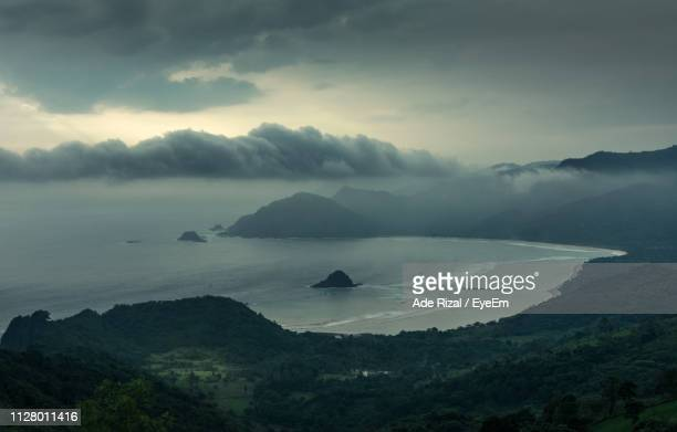 scenic view of sea and mountains against sky - ade rizal stock photos and pictures
