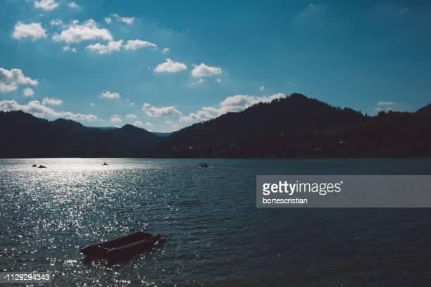 scenic view of sea and mountains against sky - bortes foto e immagini stock