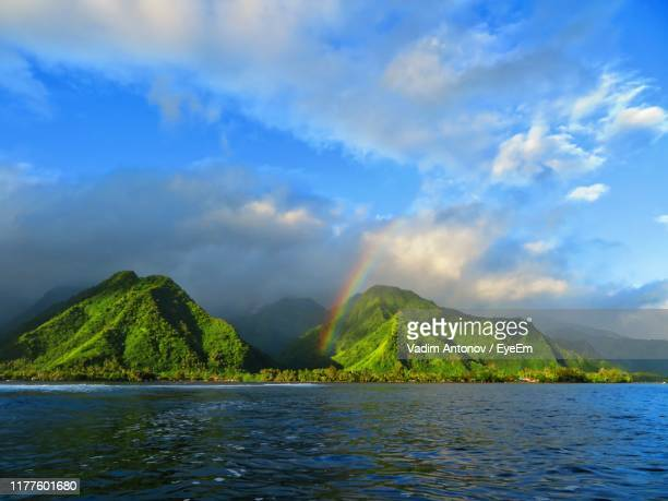 scenic view of sea and mountains against sky - タヒチ ストックフォトと画像