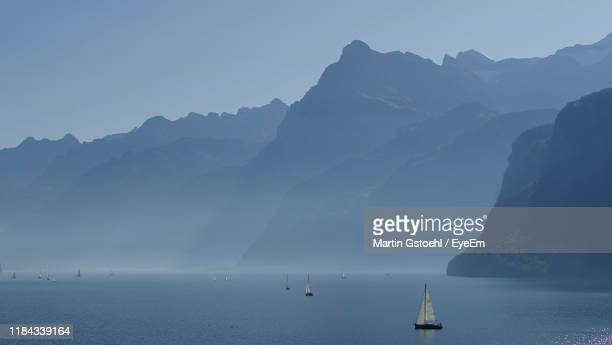 scenic view of sea and mountains against sky - schwyz stock pictures, royalty-free photos & images