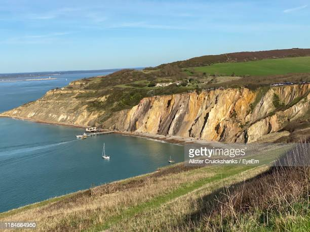 scenic view of sea and mountains against sky - totland bay stock pictures, royalty-free photos & images
