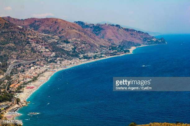 scenic view of sea and mountains against sky - naxos sicily stock pictures, royalty-free photos & images