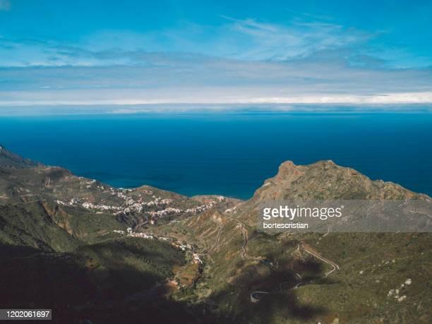 scenic view of sea and mountains against sky - bortes imagens e fotografias de stock