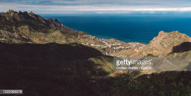 scenic view of sea and mountains against sky - bortes stock-fotos und bilder