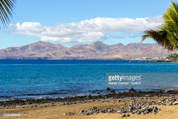 scenic view of sea and mountains against sky - puerto del carmen stock pictures, royalty-free photos & images