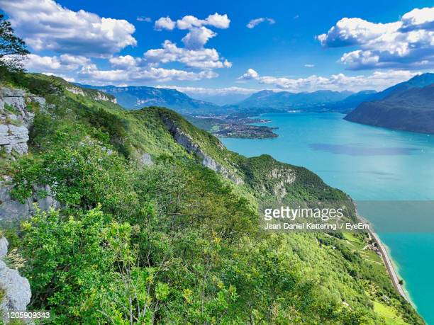 scenic view of sea and mountains against sky - lac du bourget photos et images de collection