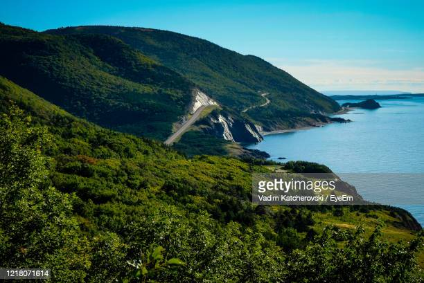 scenic view of sea and mountains against sky - cape breton island stock pictures, royalty-free photos & images