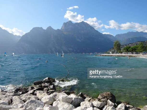 scenic view of sea and mountains against sky - kanjana kongthong foto e immagini stock