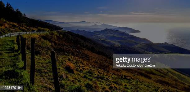 scenic view of sea and mountains against sky - オンダリビア ストックフォトと画像
