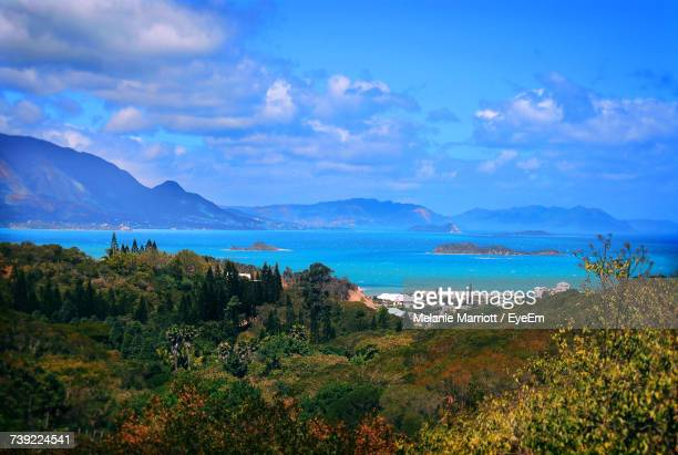 scenic view of sea and mountains against sky - new caledonia stock photos and pictures