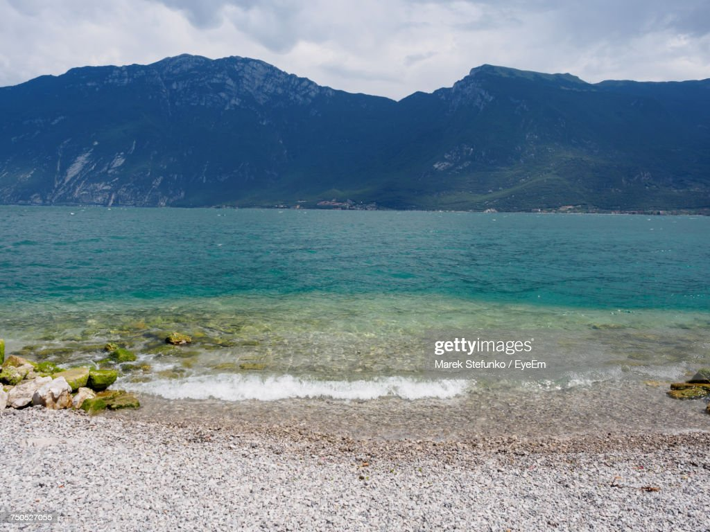 Scenic View Of Sea And Mountains Against Sky : Stock Photo