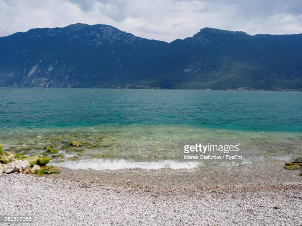 scenic view of sea and mountains against sky - marek stefunko stockfoto's en -beelden