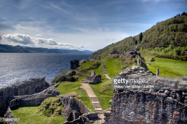 scenic view of sea and mountains against sky - loch ness stock photos and pictures