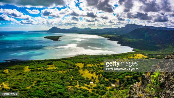 scenic view of sea and mountains against sky - port louis stock photos and pictures