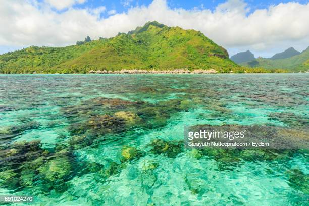 scenic view of sea and mountains against sky - tahiti stock pictures, royalty-free photos & images