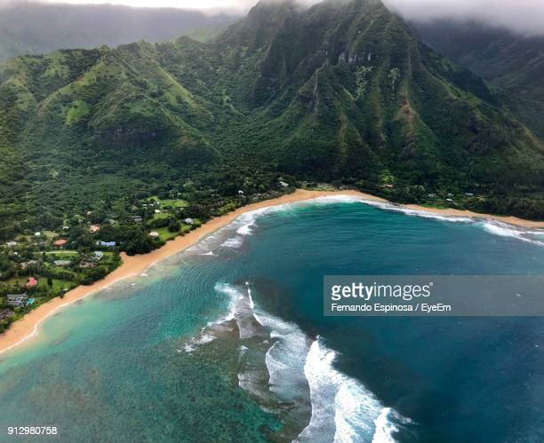 scenic view of sea and mountains against sky - waimea valley stock photos and pictures