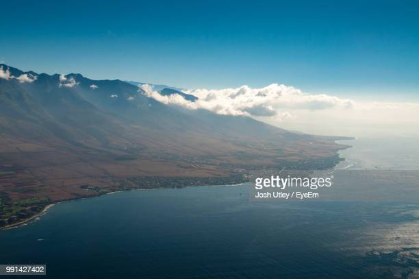 scenic view of sea and mountains against sky - josh utley stock pictures, royalty-free photos & images
