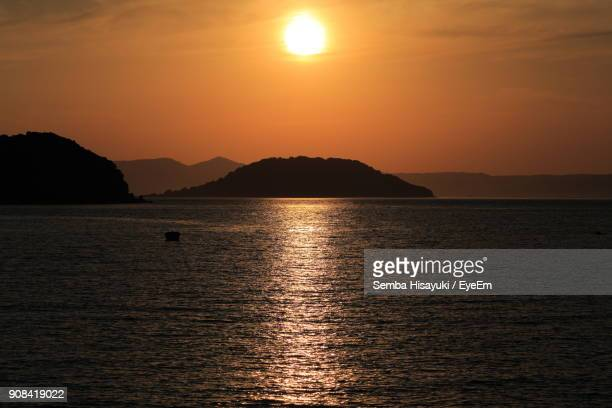 Scenic View Of Sea And Mountains During Sunset