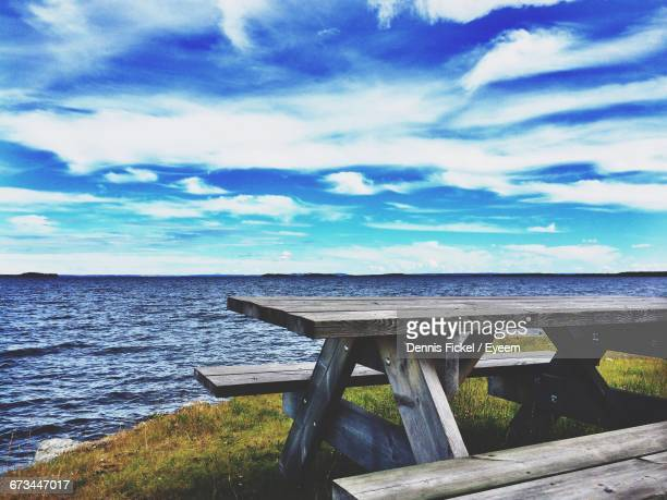 scenic view of sea and picnic table against cloudy sky - picnic table stock pictures, royalty-free photos & images