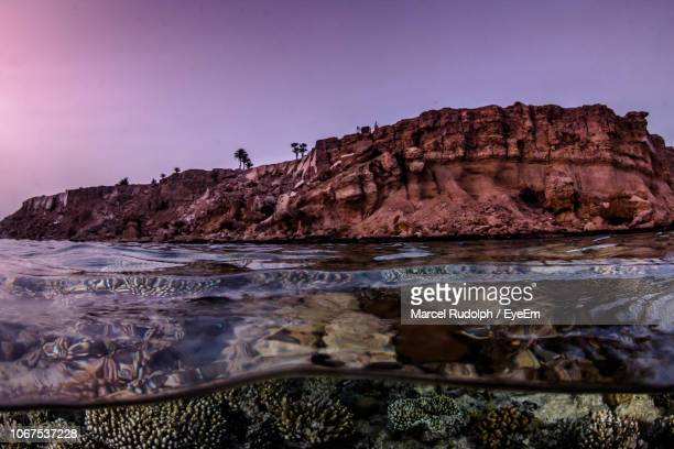 scenic view of sea and rock formation against clear sky during sunset - red sea stock pictures, royalty-free photos & images