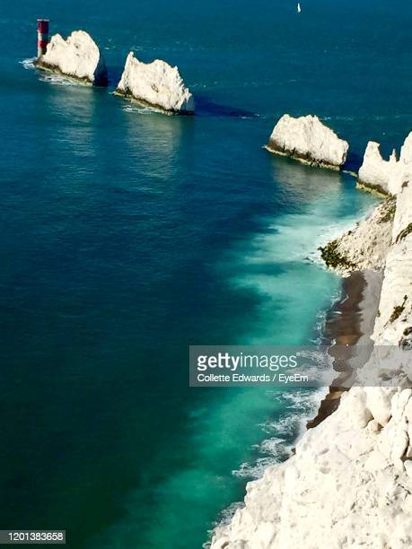 scenic view of sea and rock formation - totland bay stock pictures, royalty-free photos & images
