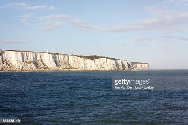Scenic View Of Sea And Rock Formations Against Sky On Sunny Day